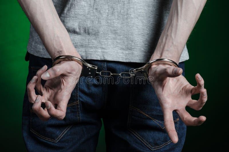 Fängelse och beslagit ämne: man med handbojor på hans händer i en grå T-tröja och jeans på ett mörker - grön bakgrund i stuen arkivbild
