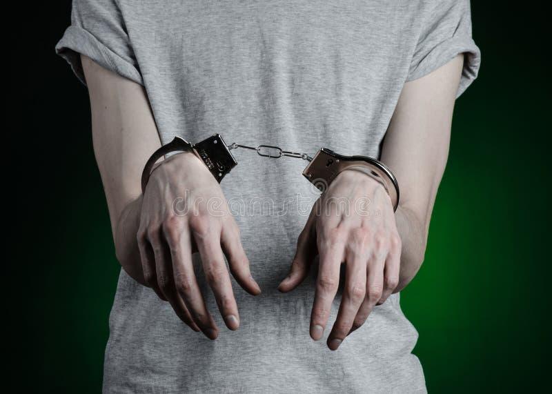 Fängelse och beslagit ämne: man med handbojor på hans händer i en grå T-tröja och jeans på ett mörker - grön bakgrund i stuen arkivfoto