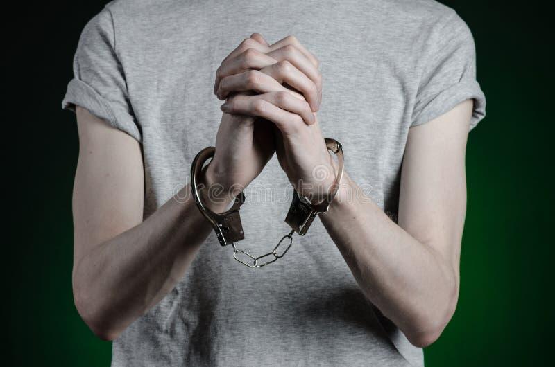 Fängelse och beslagit ämne: man med handbojor på hans händer i en grå T-tröja och jeans på ett mörker - grön bakgrund i stuen royaltyfria foton