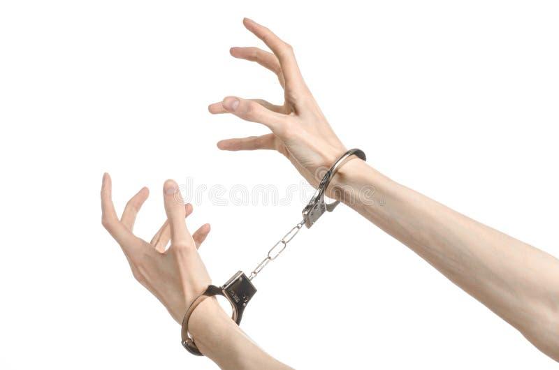 Fängelse och beslagit ämne: manhänder med handbojor som isolerades på vit bakgrund i studio, satte handbojor på mördaren arkivfoton