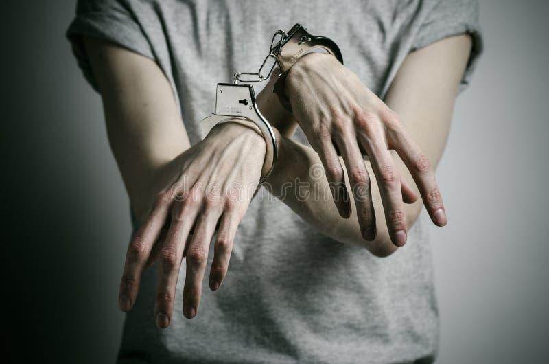 Fängelse och beslagit ämne: mannen med handbojor på hans händer i en grå T-tröja på en grå bakgrund i studion, satte på handbojor royaltyfri bild