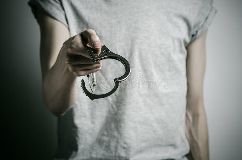 Fängelse och beslagit ämne: mannen med handbojor på hans händer i en grå T-tröja på en grå bakgrund i studion, satte på handbojor royaltyfri fotografi