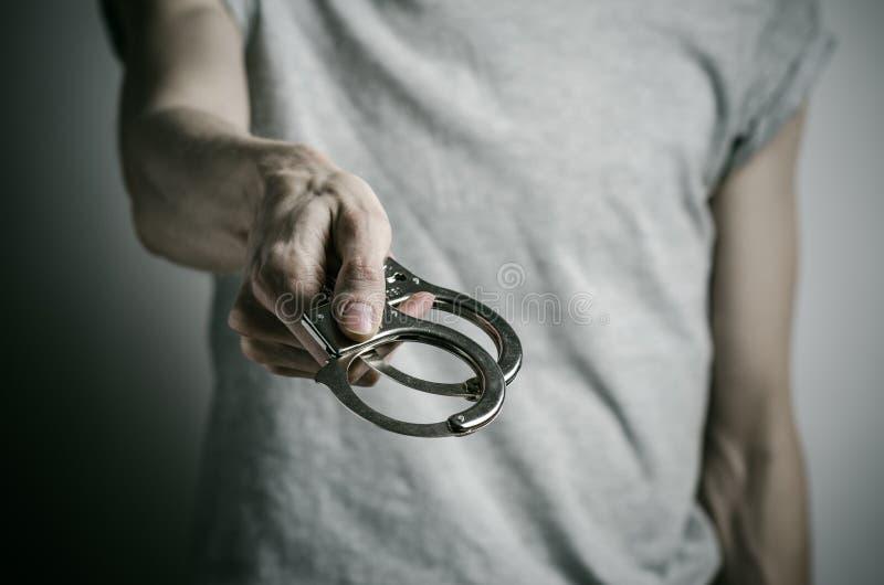 Fängelse och beslagit ämne: mannen med handbojor på hans händer i en grå T-tröja på en grå bakgrund i studion, satte på handbojor arkivfoto