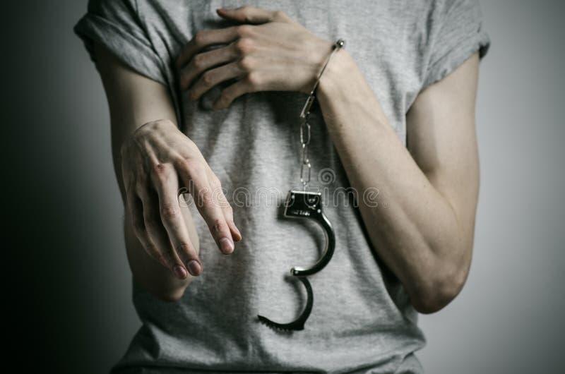 Fängelse och beslagit ämne: mannen med handbojor på hans händer i en grå T-tröja på en grå bakgrund i studion, satte på handbojor arkivfoton
