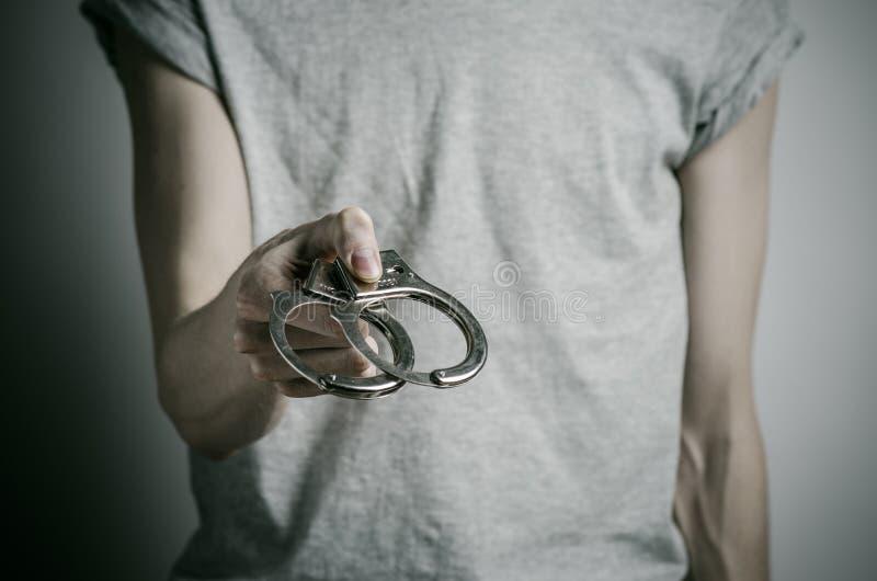 Fängelse och beslagit ämne: mannen med handbojor på hans händer i en grå T-tröja på en grå bakgrund i studion, satte på handbojor fotografering för bildbyråer