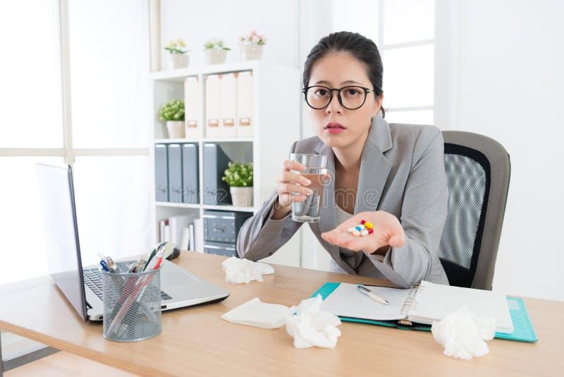Fängt junger weiblicher Büroangestellter der Traurigkeit Kälte stockfotografie