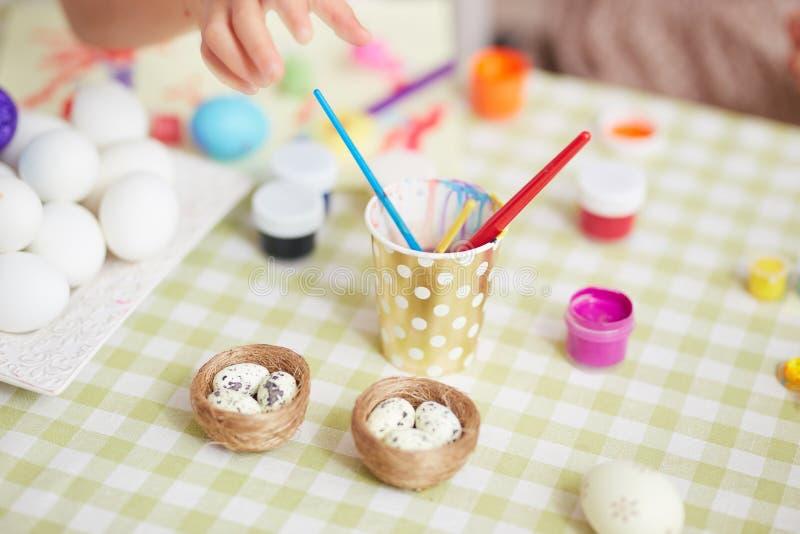 Färben der Eier für die Ostern-Tabelle in der gemütlichen hellen Küche lizenzfreie stockbilder