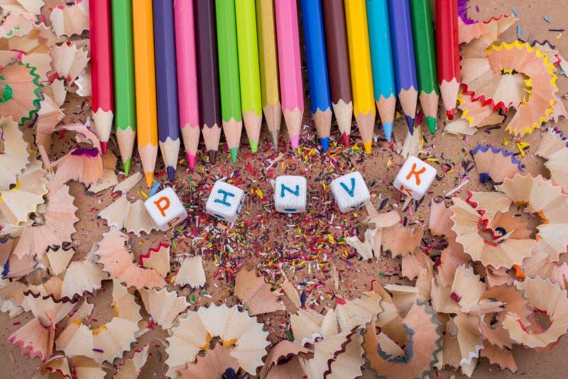 Färben Sie Bleistifte und Buchstabewürfel auf Bleistiftschnitzeln lizenzfreie stockfotografie
