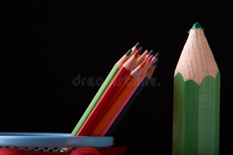 Färben Sie die Bleistifte und großen grünen Bleistift oben solated auf schwarzem Hintergrundabschluß stockfoto