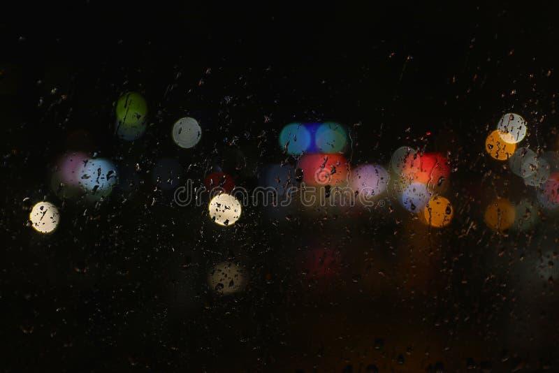Färben Sie Lichter auf dem regnerischen dunklen Fensterglas lizenzfreie stockbilder