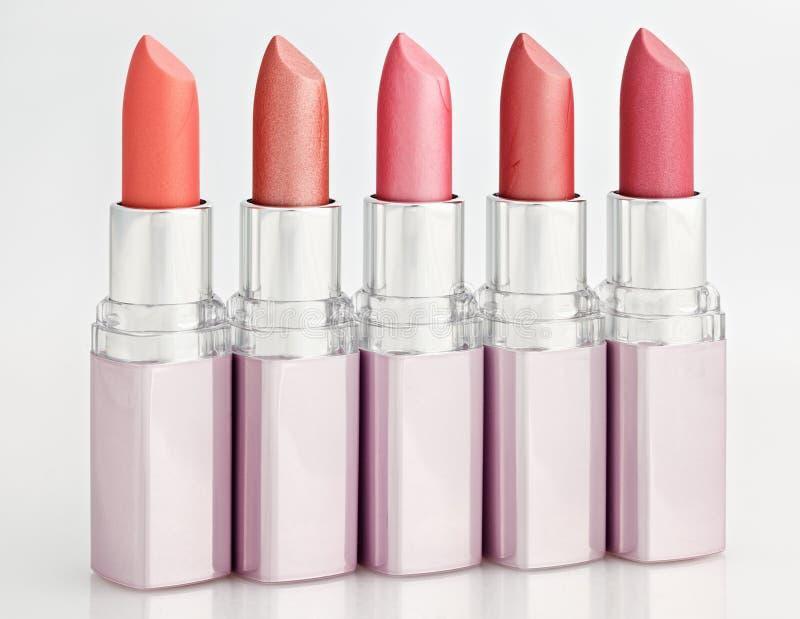 Färben Sie Lippenstifte angeordnet in der Zeile, die auf Weiß getrennt wird stockfotografie