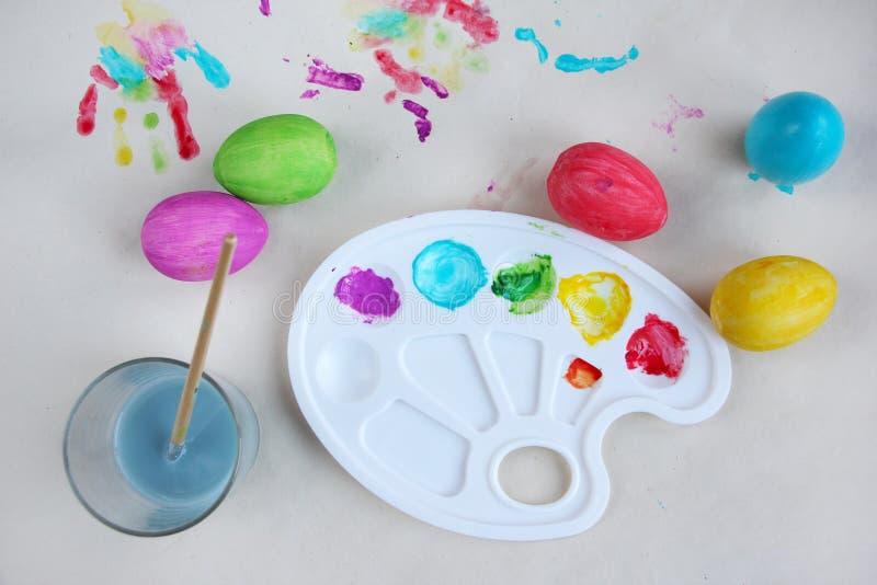 Färbende Ostereier Farben, Palette, Bürste, Wasserschüssel und farbige Eier auf Tabelle, flache Lage lizenzfreies stockbild