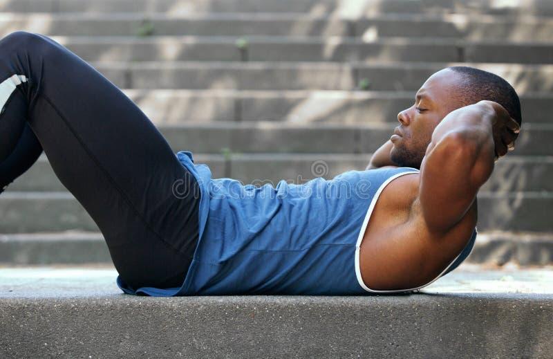 Färdig afrikansk amerikanman som gör mageknastranden fotografering för bildbyråer