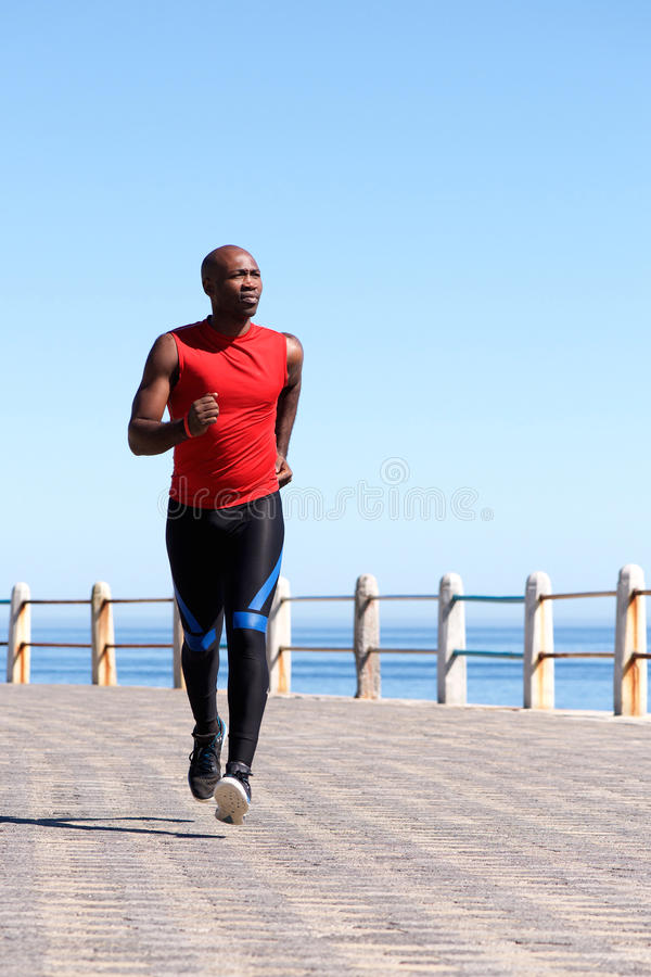 Färdig afrikansk man som joggar på sjösidapromenad royaltyfri bild