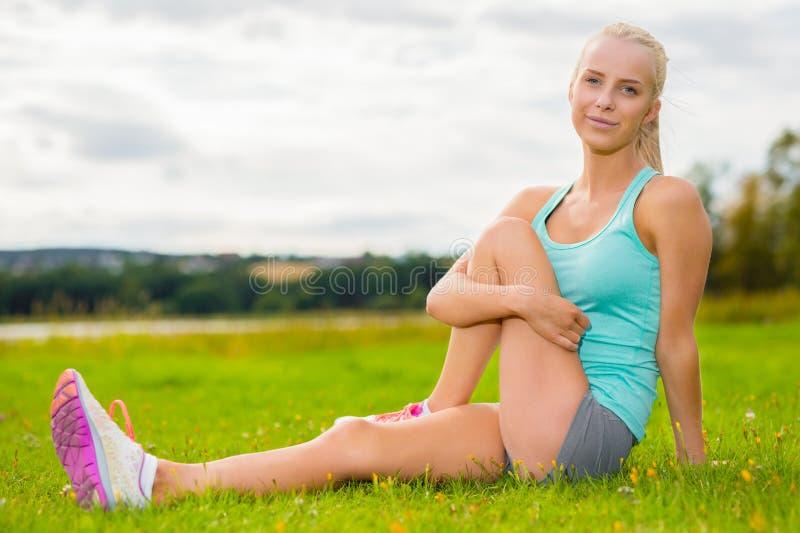 Färdig blond kvinnasträckning som är utomhus- på gräset arkivfoto