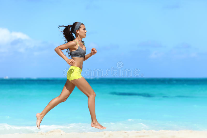 Färdig för flickalöpare för kvinnlig idrottsman nen spring på stranden royaltyfri foto