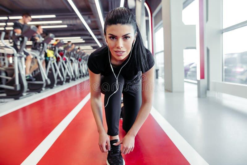 Färdig flicka ner som gör skosnöre på konditionidrottshallen, innan att köra övningsgenomkörare royaltyfri foto