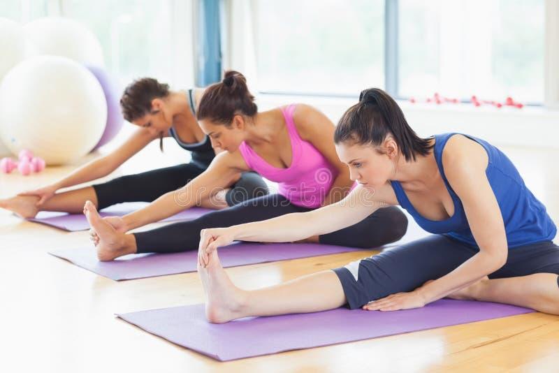 Färdig grupp som sträcker ben på mats på yogagrupp arkivfoton