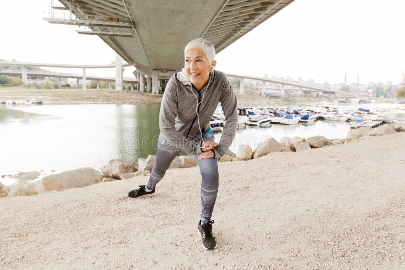 Färdig hög kvinna som gör den utomhus- konditionövningen arkivfoton