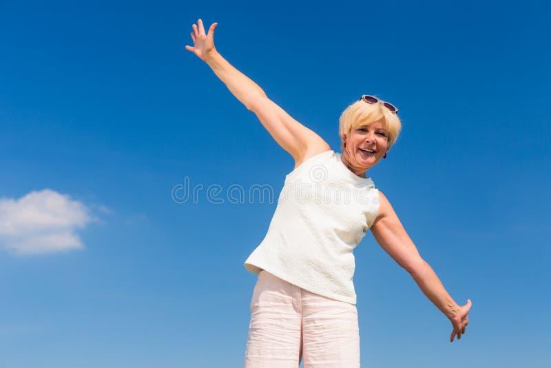 Färdig hög kvinna som upp till ser himlen, medan tycka om avgång royaltyfria bilder