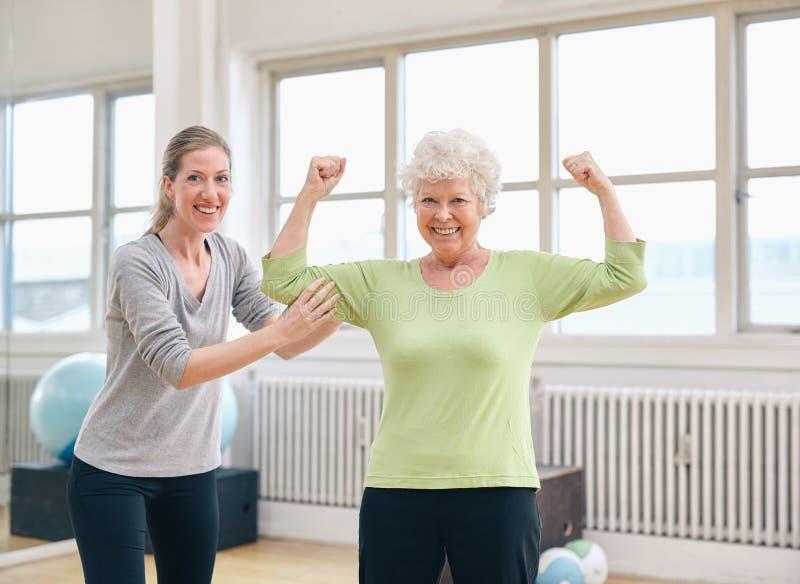 Färdig hög kvinna som visar henne biceps på idrottshallen royaltyfri bild