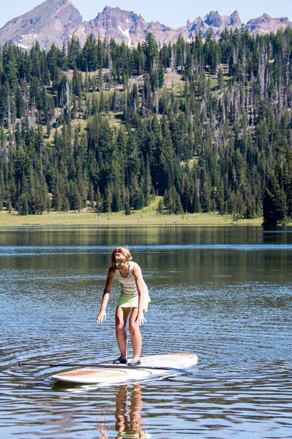 Färdig kvinna för aktiv på en ställning upp paddleboardrodd på Todd Lake i kaskad sjöområdet i krökningen Oregon arkivfoto