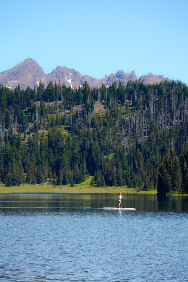 Färdig kvinna för aktiv på en ställning upp paddleboardrodd på Todd Lake i kaskad sjöområdet i krökningen Oregon på en solig dag fotografering för bildbyråer