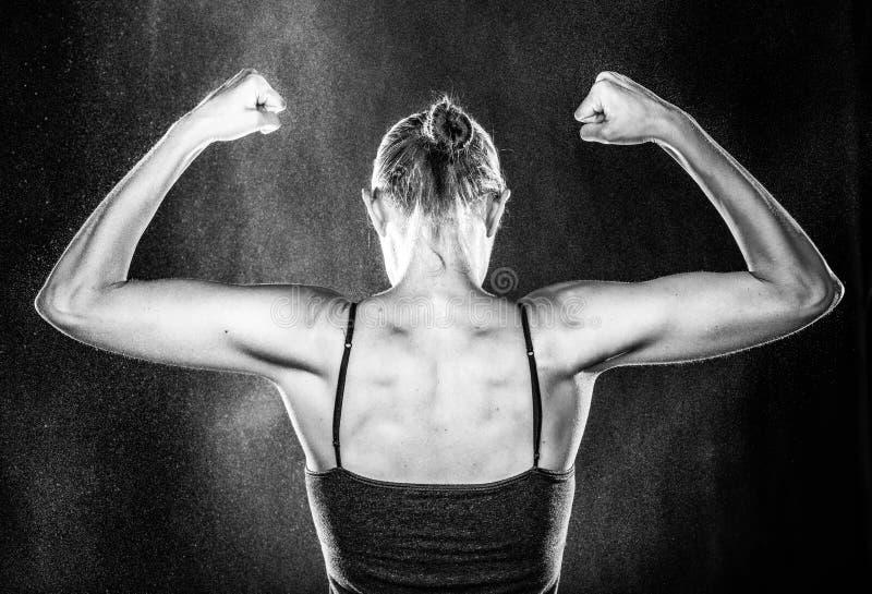 Färdig kvinna för idrottshall som visar hennes arm och tillbaka muskler royaltyfria bilder