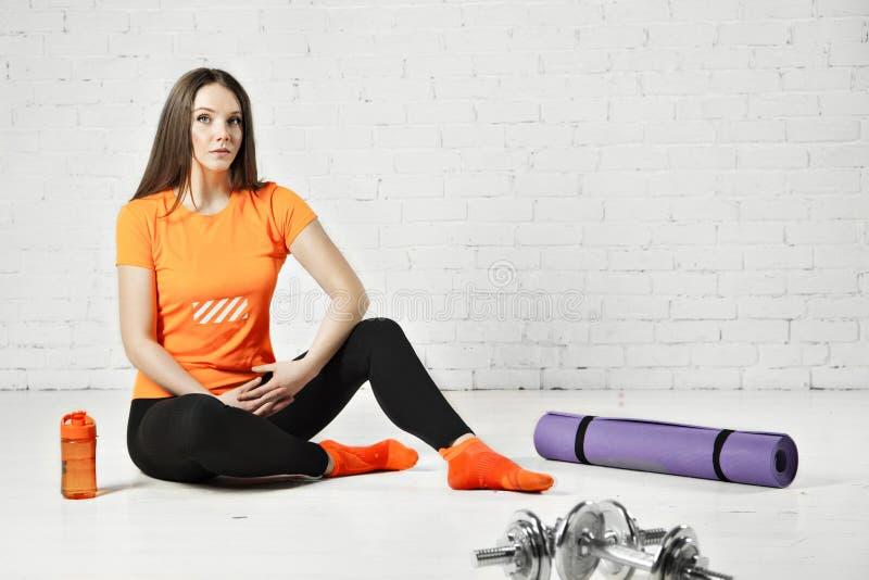 Färdig kvinna för sport som poserar i en idrottshall med utrustning, hanteln och det utbildande blocket arkivfoton