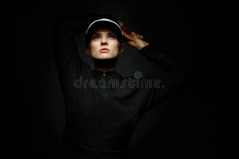 Färdig kvinna i tennisskärmen som ser upp mot svart bakgrund arkivfoto