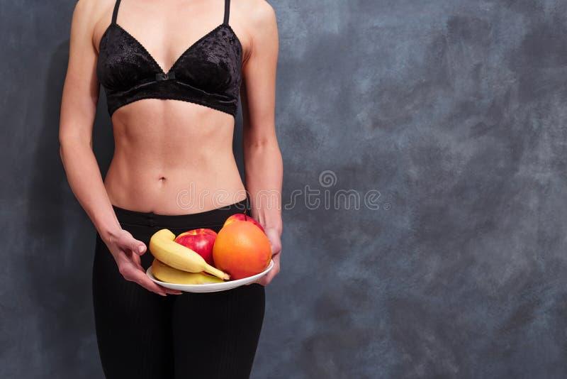 Färdig kvinna med en platta av frukter, kopieringsutrymme Banta sjukvården, arkivfoton