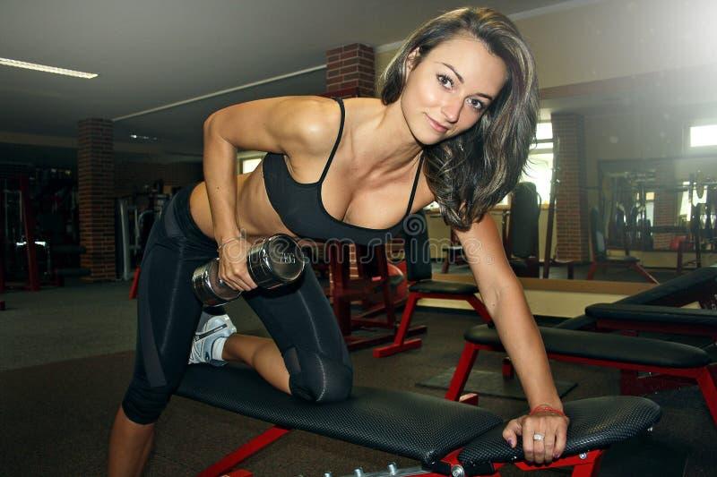 Färdig kvinna på idrottshallen som gör en rad för en arm royaltyfri bild