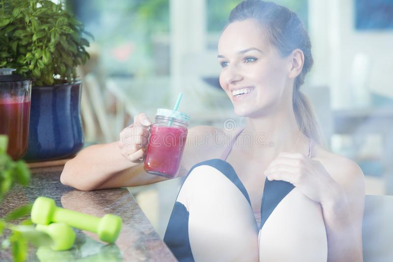 Färdig kvinna som dricker den röda smoothien royaltyfri foto