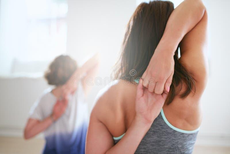 Färdig kvinna som gör gomukhasana i yogagrupp royaltyfria foton