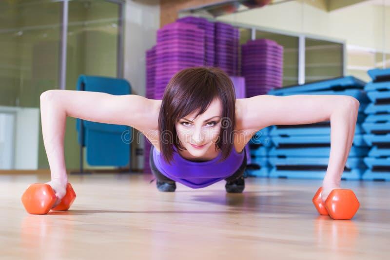 Färdig kvinna som gör push-UPS med hantlar på ett golv i en idrottshall royaltyfri foto