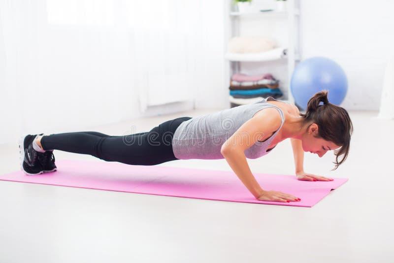 Färdig kvinna som gör push-UPS på golvet i henne arkivfoton