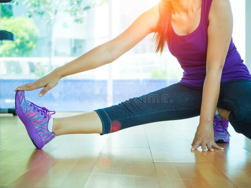 Färdig kvinna som sträcker hennes ben för att värma upp i idrottshallrum med konditionutrustningar i bakgrund royaltyfria foton