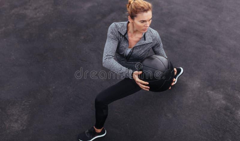 Färdig kvinna som utomhus övar med medicinbollen arkivfoto