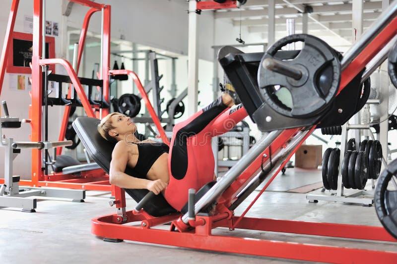 Färdig kvinnautbildning lägger benen på ryggen på en bensimulator på idrottshallen arkivbilder
