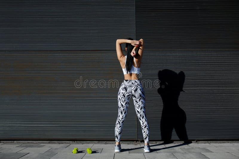 Färdig kvinnlig i sportswear som utomhus övar på svart bakgrund royaltyfri bild