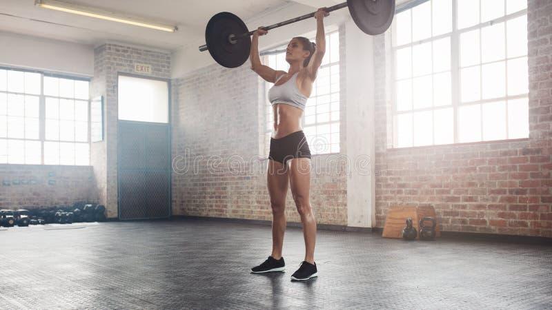 Färdig kvinnlig idrottsman nen som gör att lyfta för tungvikt arkivfoto