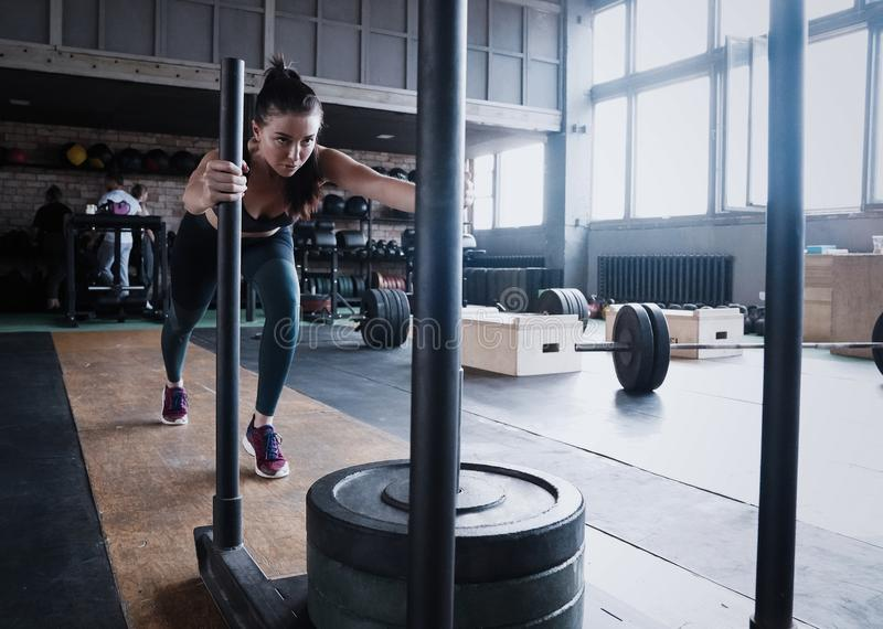 Färdig kvinnlig idrottsman nen som utarbetar i idrottshallen ?va f?r Crossfit kvinna arkivbilder