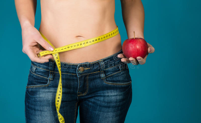 Färdig kvinnlig kropp med äpplet och mätabandet Sund kondition och äta livsstilbegrepp royaltyfri bild