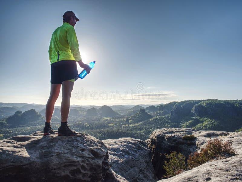 Färdig löpare i sportdräkt som dricker vattnet från sportflaskan royaltyfri foto