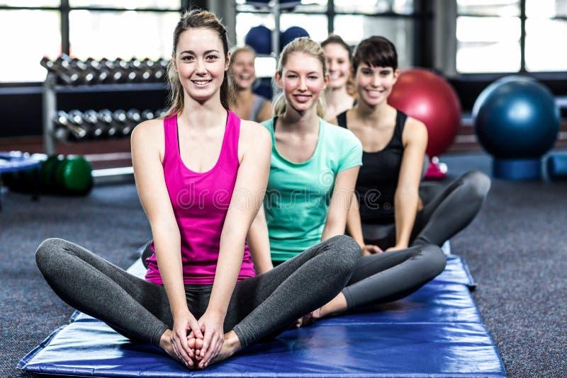 Färdig le grupp som gör yoga royaltyfri fotografi