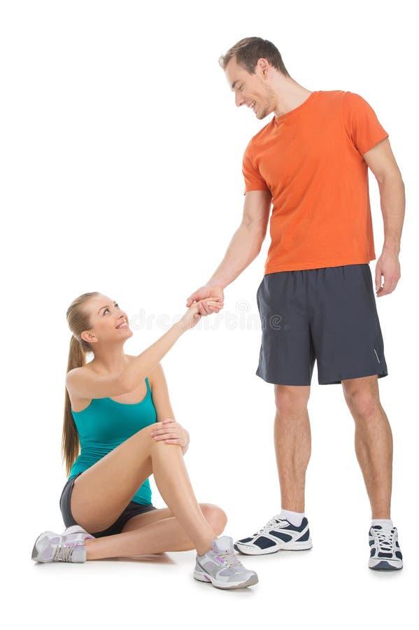 Färdig man som hjälper den attraktiva kvinnan att stiga. arkivbilder