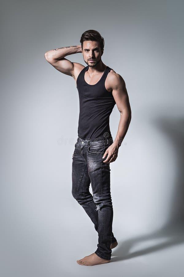 Färdig man som poserar i jeans och skjorta fotografering för bildbyråer