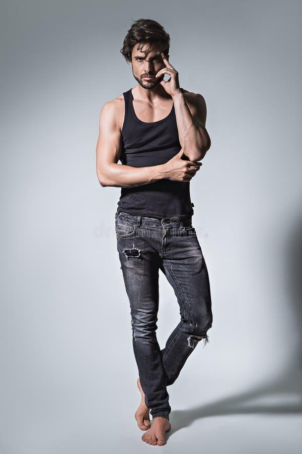 Färdig man som poserar i jeans och skjorta royaltyfri foto