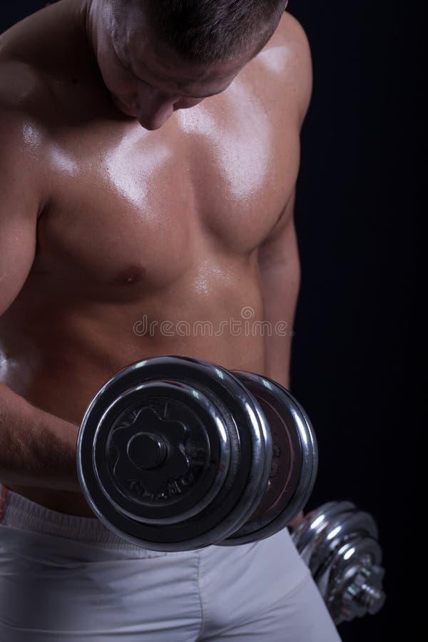 Färdig muskulös man som övar med hanteln arkivfoton