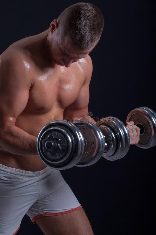 Färdig muskulös man som övar med hanteln arkivbilder